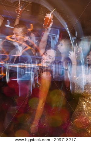 Happy party with alcohol at night club in blurred motion. Joyful friends at Christmas discotheque, active New Year company with drinks, modern youth life