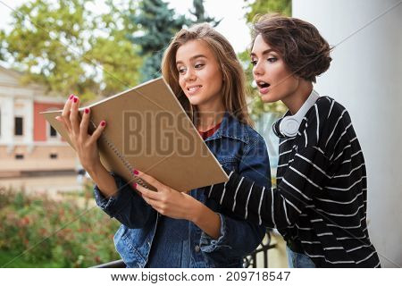 Two young pretty teenage girls studying together with a book outdoors