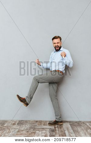 Full length image of happy screaming bearded man in business clothes rejoice and looking at the camera over gray background
