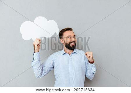 Happy bearded man in business clothes holding blank speech cloud and looking away over gray background