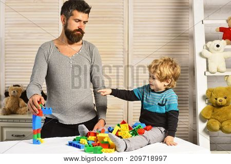 Dad and kid build of plastic blocks. Family and childhood concept. Father and son with interested faces create colorful robot with toy bricks. Boy points at mans creation on wooden wall background