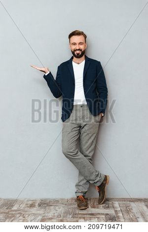 Full length image of happy bearded man in business clothes with arm in pocket holding copyspace on the pound and looking at the camera over gray background