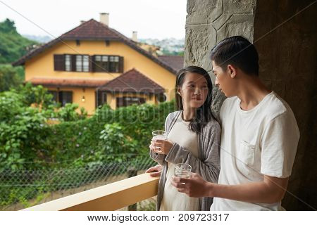 Young couple drinking water when standing on balcony in the morning