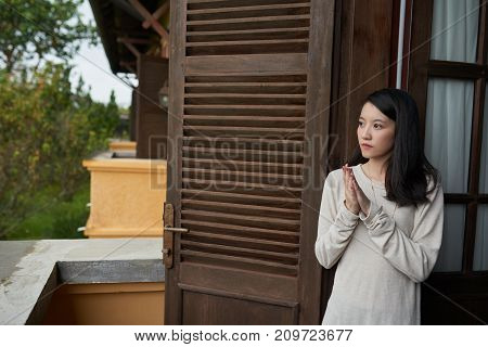 Lovely attractive Asian young woman standing on balcony of hotel room