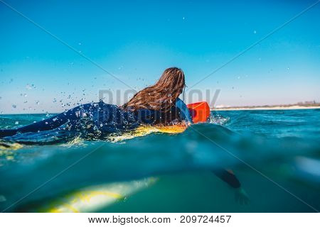 Surf girl rowing on the surfboard. Woman with surfboard in ocean during surfing. Surfer and ocean