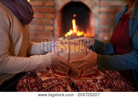 Wife giving present to her husband when they are sitting under blanket