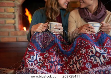Cheerful young couple under warm blanket drinking hot tea