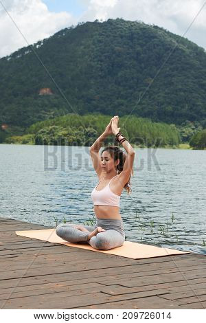 Pretty Vietnamese young woman sitting in lotus position on wooden pier