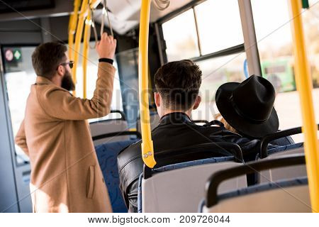 back view of leather jackets sitting together in city bus