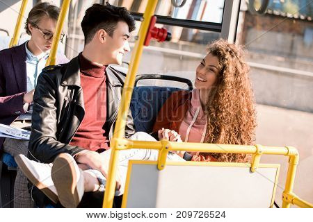 happy young couple smiling each other while sitting together in bus