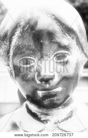 Detail of a sculpture of a young girls face in black and white.