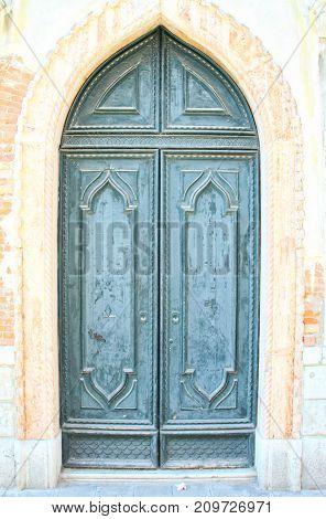A blueish green Venetian door in an arch.