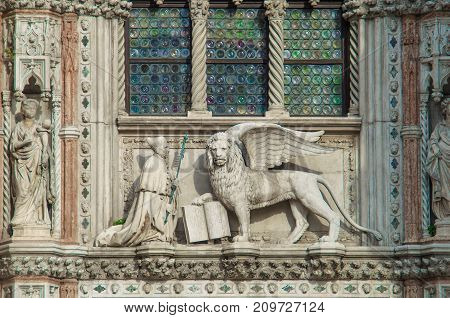 VENICE ITALY - SEPTEMBER 29 2017: Sculptures on Porta della Carta of the Doge's Palace in Venice Italy. The Doge kneeling before the winged Lion of St Mark.