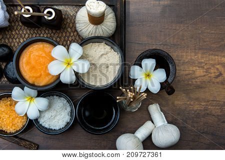 Thai spa composition treatments aroma therapy with candles and Plumeria flowers on wooden table close up. Healthy Concept.