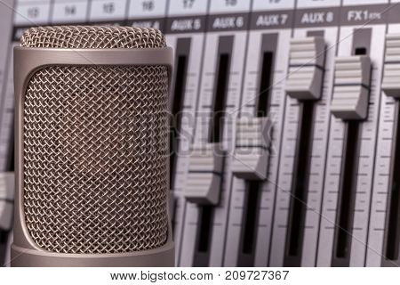 Professional recording microphone with studio audio mixer in the background. Vocal song recording equipment in close up.