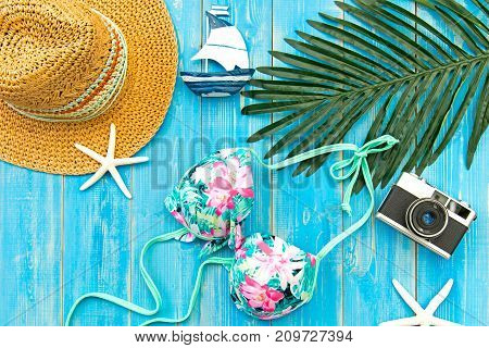Summer Fashion woman big hat and accessories vintage camera go to travel in the beach. Tropical sea.Unusual top view blue background. Summer Concept.