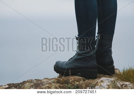 Woman hiker legs in big boots on mountain peak cliff, close up
