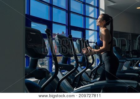 Beautiful young girl is engaged on simulators at the window in the gym