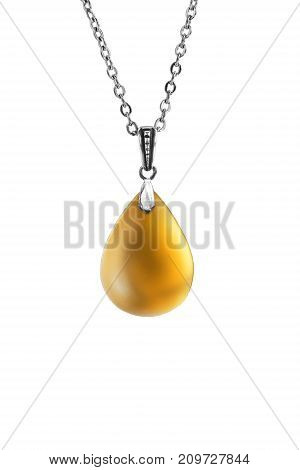 Yellow amber drop shaped pendant hanging on silver chain isolated over white