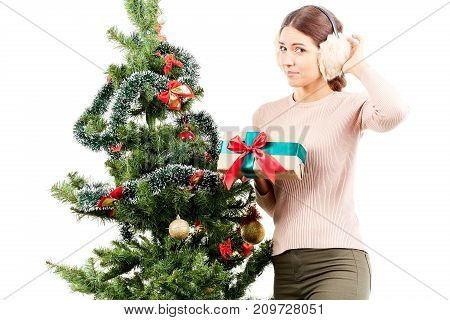 Portrait of beautiful woman in earmuffs posing near Christmas tree