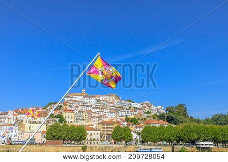 Panoramic view of old Coimbra city and Mondego river from Santa Clara bridge with flag of Coimbra flying on foreground.