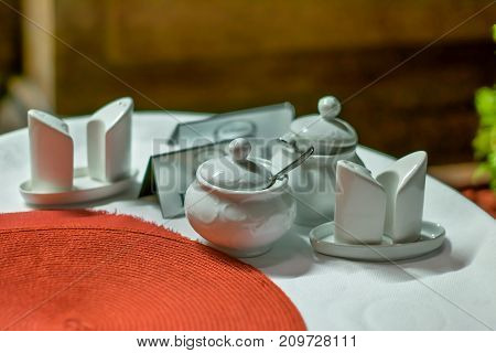 sugar bowls, porcelain cups for coffee or tea and different ceramic dishes on a table in a cafe
