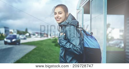 woman traveler with backpack stands and waits for a bus at a bus stop
