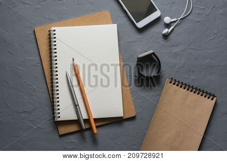 Business or education background. Notebooks phone headphones pencils pens watch on grey background top view. Blank notepad with space for text