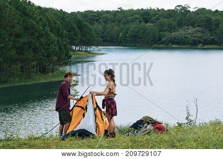 Vietnamese young couple assembling tent by the river