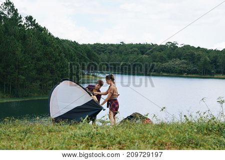 Young woman helping her boyfriend to assemble a tent