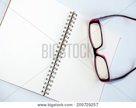 Blank Page Of A Notebook And Eyeglasses