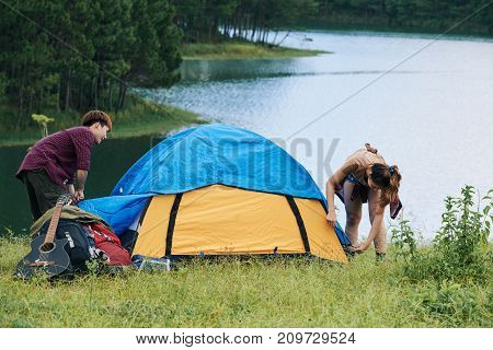 Travelers assembling tent to spend night by the lake