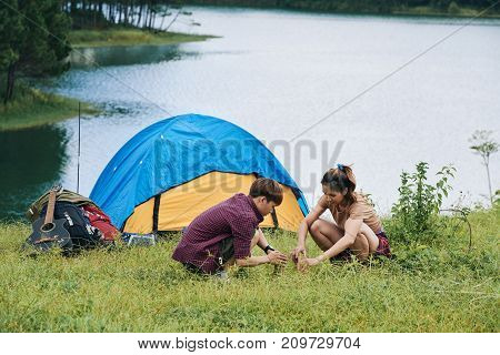 Vietnamese travelers making campfire by tent together