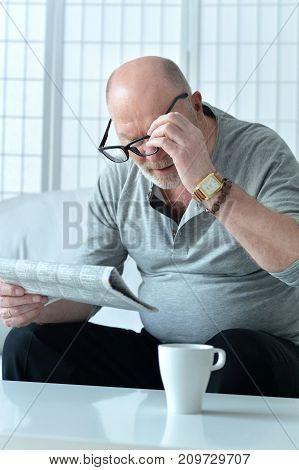 Portrait of a man sittingand reading newspaper