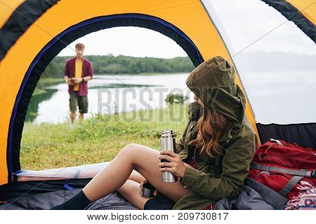 Young woman sitting in tent and drinking tea when her boyfriend is making campfire
