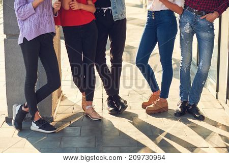 Legs of group of casual young people. Youth fashion. Crop of diverse informal students standing in row outdoors urban background
