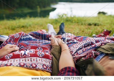 Couple of travelers holding hands when lying under blanket by the lake