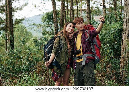 Young Asian hikers couple taking selfie on smartphone in forest