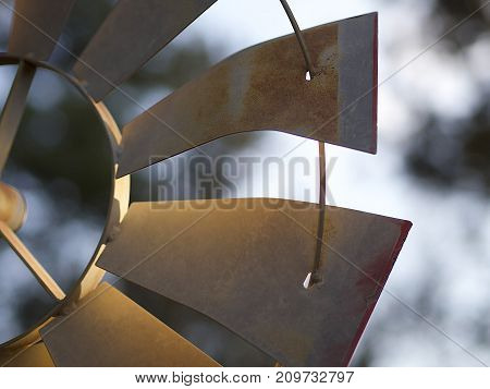 Detailed blades on a decorative retro windmill for landscaping on a nice evening.