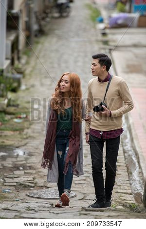 Young travelers walking in city street with camera
