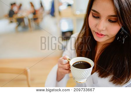 Portrait of beautiful woman holding a cup of coffee in her hand in blur background coffee shop she drink coffee in the morning vintage style