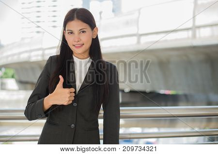 beautiful business woman smile and showing thumb up in the city business success concept