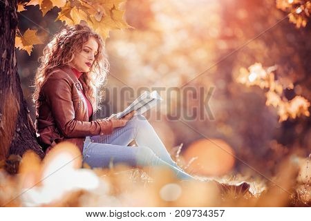 Young beautiful girl in the autumn park reading a book.