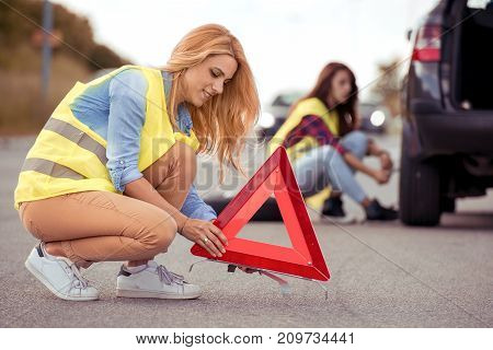 Two young woman on the road having problem with a car. Broken down car on the road. Traveling and transportation concept.
