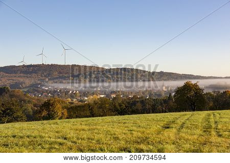 rural landscape grass field and trees in foreground fog mist over village in middle and hills and wind turbines in background against cloudless blue sky