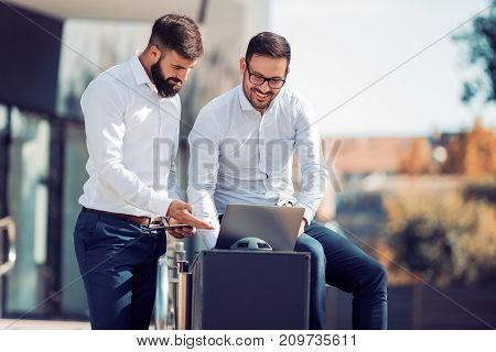 Two young businessmen talking outdoors,having a break.