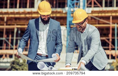 Two young architects or engineers discussing a project plan.