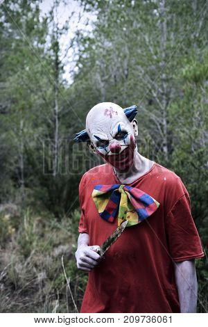 closeup of a scary evil clown in the woods wearing a dirty and ragged red costume, with a big knife in his hand