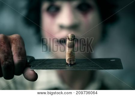 closeup of a scary disfigured man holding a rusty and bloody cleaver in front of his face with a bloody amputated finger on it