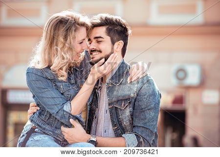 Portrait of romantic couple in love hugging on the street. Falling in love